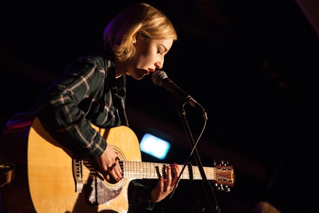 Svenja Schimmelpfennig zupft mit roten Fingernägeln auf einer Akustikgitarre und haucht mit geschlossenen Augen ins Mikrofon