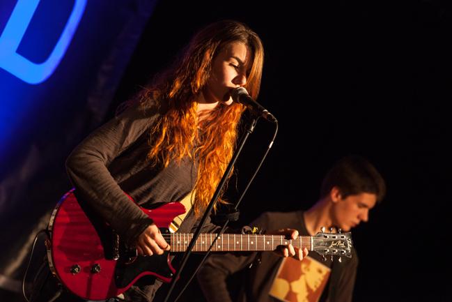 Frontsängerin von The cuckoo, spielt auf einer roten E Gitarre, singt mit roten locken im Gesicht
