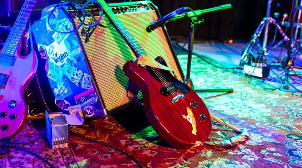 Gitarren, Verstärker,Kabel und ein leicht diffuses Drumset im Hintergrund, auf dem typischen Pflasterstrandteppich